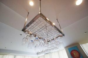 ワイングラスハンガーを設置、キッチンのアクセントにビビットなカラーのイタリア製のタイルを貼った施工事例です。